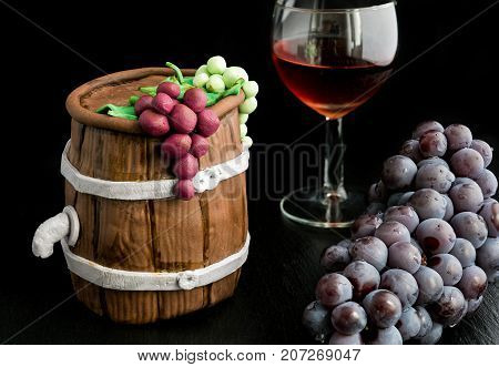 Handmade cake of sugar paste inspired from wine barrels with a glass of red wine and a bunch of grapes