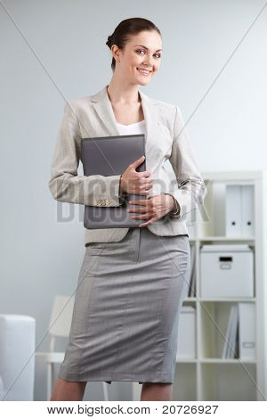 Portrait of smiling businesswoman looking at camera in office