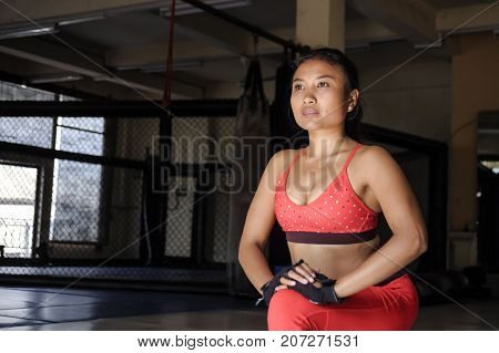 concentrated face expression of young sweaty Asian woman in sport clothes stretching legs relaxing muscles on gym dojo after hard training workout and healthy sporty lifestyle concept