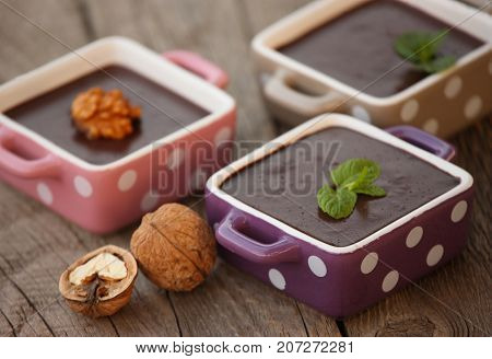 Chocolate pudding in polka dot bowls, wood background
