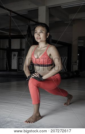 young sweaty Asian woman in sport clothes stretching legs relaxing muscles on gym dojo after hard training workout and healthy sporty lifestyle concept