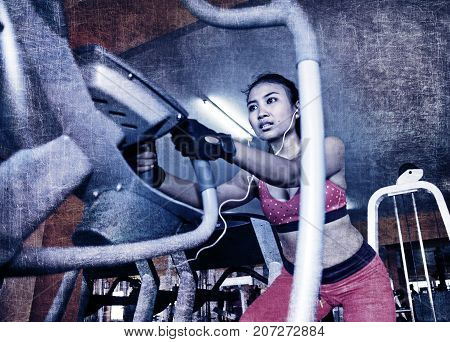 grunge harsh dramatic edit of young sexy sweaty Asian woman training hard at gym using elliptical pedaling machine gear in intense workout exercise in sport top in fitness healthy lifestyle concept
