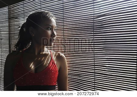 shady portrait of young beautiful Asian woman in gym sport cloths looking through Venetian blinds window in shadow sun dramatic light posing thoughtful and pensive in artistic beauty concept