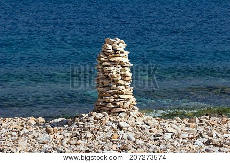 Stack of stones in balance with blue sea on background