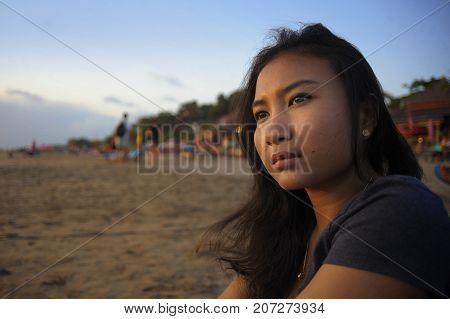 portrait of young beautiful Asian lonely woman looking to infinity lost in her thoughts sad and thoughtful sitting on sand beach in loneliness and meditation concept