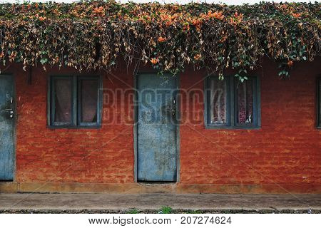 Old Nepalese simple red house with a blue windows and doors, with a flowers on the rooftop