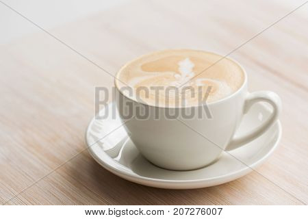 Creamy cappuccino in the white cup on wooden surface. The concept of relaxing in the cafe, relaxing time in a cafe, dreams of love, etc.