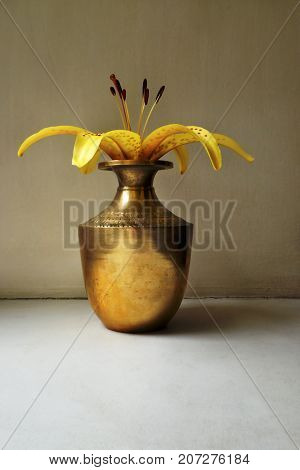 yellow lily in a vintage indian copper jar