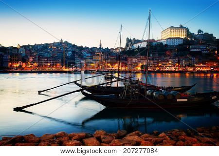Night scene of Porto old town with Douro river and traditional port wine boats, Portugal, retro toned