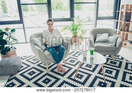 Smiling Lady In Casual Shirt And Jeans Is Sitting With Crossed Legs At The Chair At Home. She Is Wor