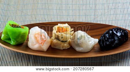 Various Dim Sum In a Row on Bamboo Plate closeup on Straw Mat background