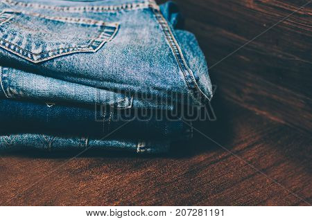 Stack of the blue jeans on wooden table