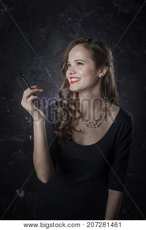 Noir film style woman in long black dress and cigarette in left hand standing side to camera. Female has a long dark hair posing with a pencil in her hand. Black and white photography. Old fashion photo