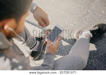 man athlete sitting on the street with mobile phone listening to music. City workout with smart gadgets and sport applications.