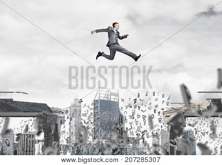 Businessman jumping over gap with flying letters in concrete bridge as symbol of overcoming challenges. Cityscape on background. 3D rendering.
