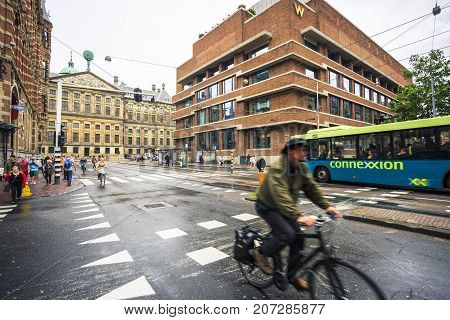 AMSTERDAM NETHERLANDS - JUNE 21 2016: Wide picture of a crossing with people riding bikes the W Amsterdam a 5 stars hotel in the right and the Amsterdam Royal Palace in the left in a cloudy day. Amsterdam Netherlands.