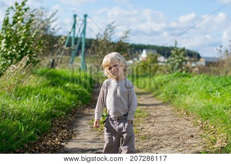 Seriouse blond boy staying embraced himself with his arms, country road to the Urals village