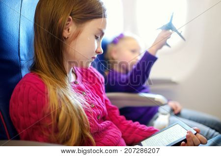 Adorable Little Children Traveling By An Airplane. Girl Sitting By Aircraft Window And Reading Her E