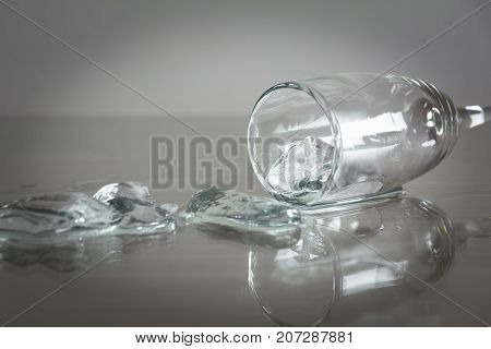 Spilled water with ice cubes on table. Glass with spilled water and ice cube.