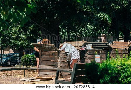 PARIS FRANCE - JUN 24 2017: Adult women composting in urban environment in dedicated spaces in the French capital. People composting placing depositing waste into recycling compost bin.
