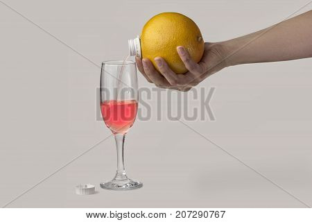 fresh juice flowing directly from the grapefruit with a bung in a tall glass. concept of a healthy lifestyle. fresh fruit juice.