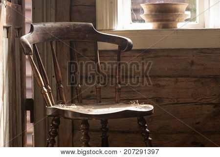 Oldfashioned design in architecture concept. Vintage wooden chair in old cottage next to window. poster