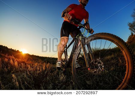 low angle view portrait of cyclist standing with mountain bike on trail at sunset