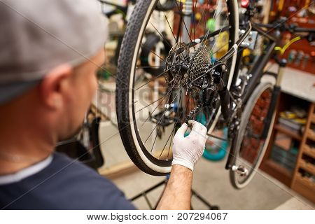 Bicycle mechanic in a workshop in the repair process. Man repair his bike. Mechanic at his workplace