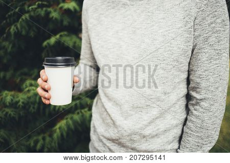 Man holding a cup of coffee in the park