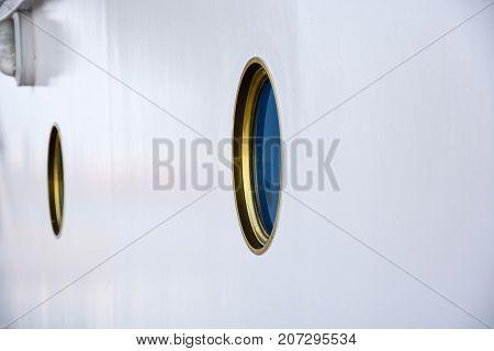 Portholes On A White Wall On A Ship