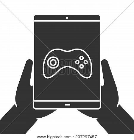 Hands holding tablet computer glyph icon. Silhouette symbol. Tablet computer with gamepad. Negative space. Vector isolated illustration