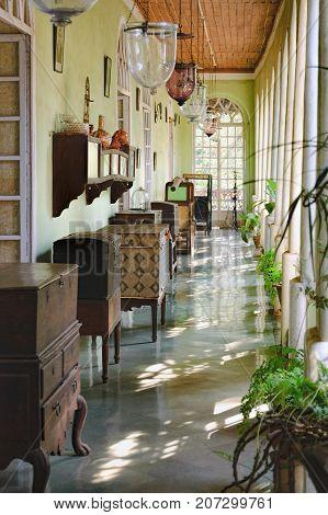 Goa, India - November 16, 2012: Menezes Braganza Pereira House - colonial Villa-Museum of Portuguese era with decoration of 16-18 century. Interior corridor with ancient objects of the Braganza family