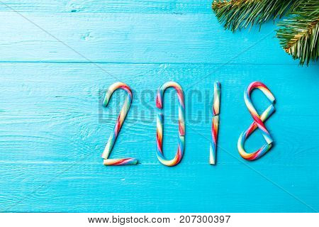 Photo of Christmas caramel sticks in form of numbers. New year 2018. Blue wooden table with spruce branches