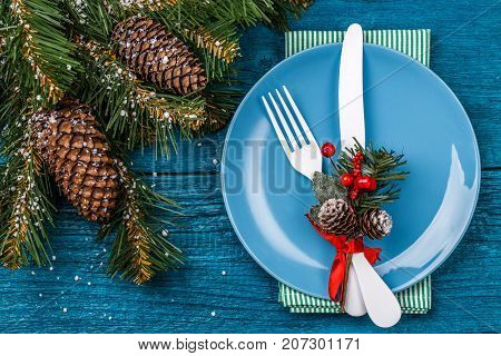 Christmas table place setting - blue table with green napkin, blue plate, white fork and knife, decorated sprig of mistletoe and christmas pine branches. New Year Clock Symbol. Christmas holidays background.