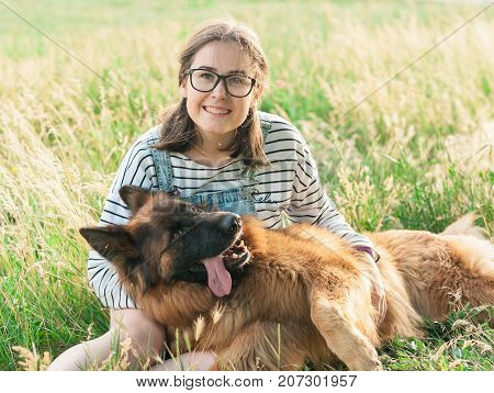 Portrait of young beautiful woman sitting and hugging her German Shepherd dog. Happiness and friendship. pet and woman.