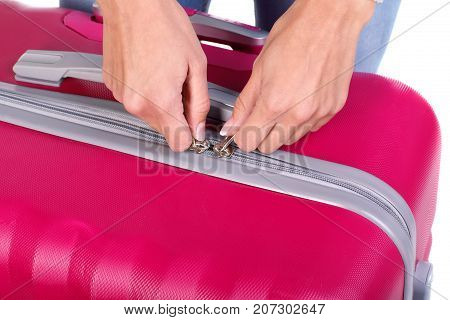 A female's hand holding huge pink suitcase and presents on the camera. A roomy and stylish suitcase for girls on a long trip around the world. Close-up of suitcase.