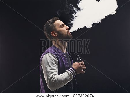 Young man vaping, studio shot. Bearded guy blowing a cloud of smoke on black background. Nicotine free smoking and vapor concept, copy space.