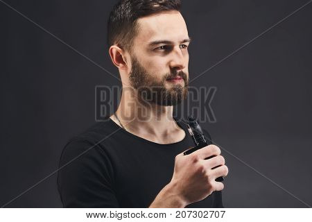 Man with vape at black studio background closeup. Young bearded guy smoking e-cigarette to quit tobacco. Nicotine free smoking and vapor concept, copy space
