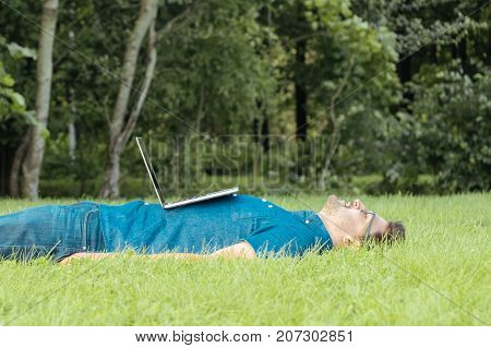 Tired Freelancer Lying In The Park With Laptop