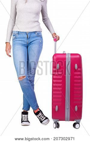 Young girl holding huge pink suitcase and presents on the camera. A roomy and stylish suitcase for girls on a long trip around the world. Full lenght of girl with suitcase.