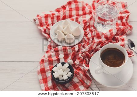Coffee time background. Treats and cup of coffee on white and red checkered cloth. Glass of water, lump sugar and meringues on white wood, copy space