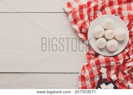 Sweet background. French meringues and lump sugar on white and red tablecloth on white wood with copy space, top view
