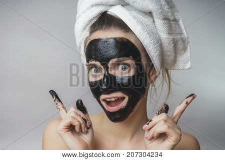 Smiling joyful woman gets black mask on face.Skin care,clean pores,exfoliation