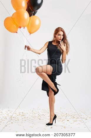 Beautiful pretty woman with orange and black balloons in sexy black dress and hight hills with long brown hair posing on camera. Full lenght of happy girl on a gray background.