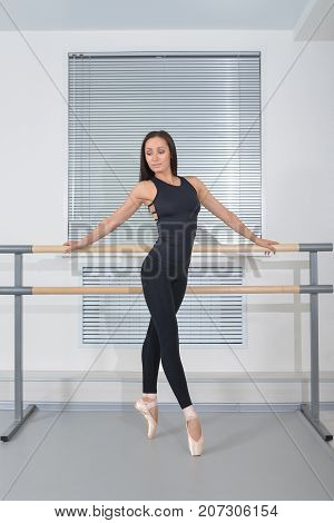 Beautiful ballerina weared in black bodysuit and white pointe shoes posing at ballet class near barre, full length portrait