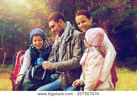 travel, tourism, hike and people concept - happy family sitting on bench and drinking hot tea from cups at camp in woods