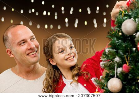 family, holidays and people concept - happy father and daughter decorating christmas tree over lights background