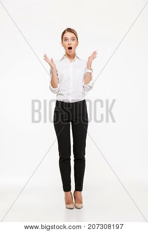 Full length image of shocked blonde business woman holding hands near head and looking at the camera with open mouth over whit background