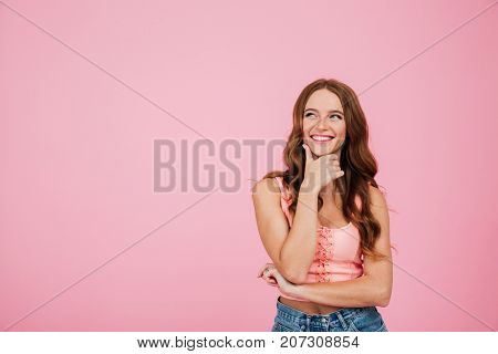 Portrait of a smiling woman in summer clothes looking away at copy space with her hand on chin isolated over pink background