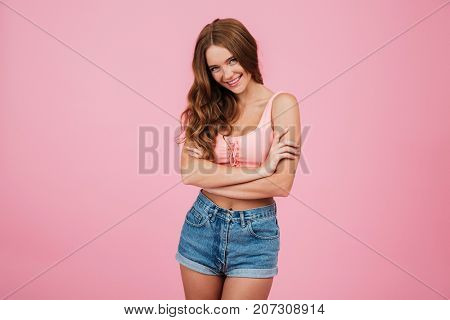 Portrait of a beautiful young woman in summer clothes standing with arms folded and laughing while looking at camera isolated over pink background